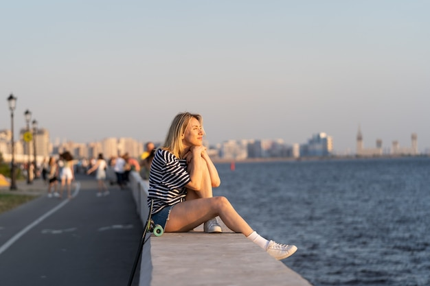 자신과 조화를 이루며 강둑에 혼자 앉아 있는 여성은 여름 일몰 자유 개념을 즐깁니다.