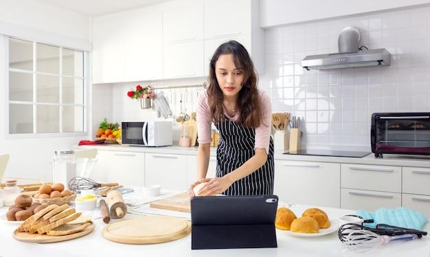 У себя дома на кухне милая молодая женщина ведет онлайн-уроки кулинарии на планшетном компьютере.