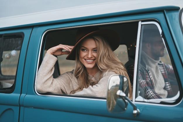 그녀 자신의 스타일로. 매력적인 젊은 웃는 여자는 밴?의 창 밖을보고 그녀의 남자 친구와 함께 자동차 여행을 즐기면서 그녀의 모자를 조정