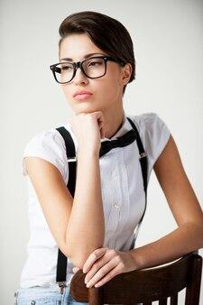 В ее собственном стиле. задумчивая молодая женщина с короткими волосами в белой рубашке и подтяжках сидит на стуле и держится за подбородок