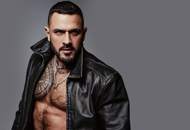 그의 잔인한 스타일. 잔인한 히스패닉 남자. 근육질의 가슴에 잔인한 문신을 한 수염 난 라틴계 남자. 잔인하고 운동, 복사 공간.