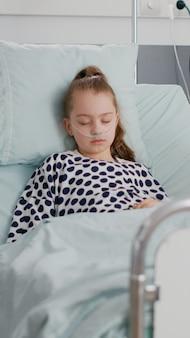 病棟で、病気の回復を祈る父親を心配しながら眠っている小さな子供患者
