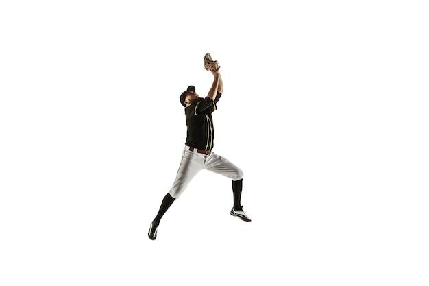 В прыжке. бейсболист, кувшин в черной униформе практикующих и тренировок, изолированные на белой стене. молодой профессиональный спортсмен в действии и движении. здоровый образ жизни, спорт, концепция движения.