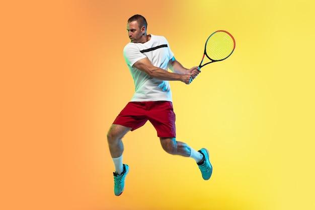 ジャンプ中。ネオンの光の中でスタジオの背景にテニスをしている一人の白人男性。スポーツゲーム中に若いプロの男性プレーヤーを動かしたり行動させたりします。動き、スポーツ、健康的なライフスタイルの概念。