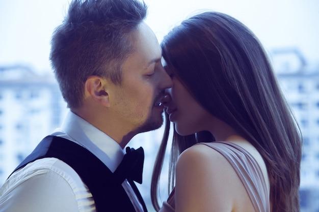 恋に情熱を持って美しいカップルが路上でお互いにキスします。情熱、愛、人間関係の概念