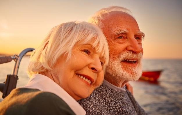 愛のクローズアップは、リラックスして笑顔を抱きながら美しく幸せな年配のカップルの肖像画