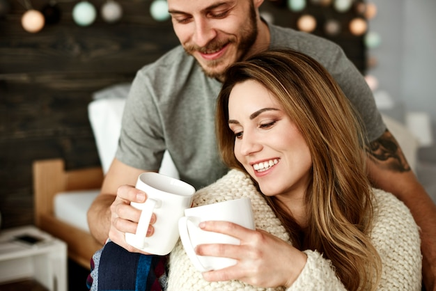 침실에서 커피를 마시는 사랑 부부