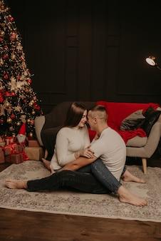 Влюбленная пара мужчина и женщина, сидящие на полу, скрестив ноги, обнимаются и целуют елку
