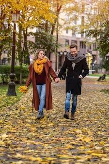 Влюбленная пара гуляет в осеннем парке, держась за руки. открытый выстрел молодой пары в любви