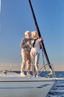 手をつないで立っている間お互いを見ている幸せな年配のカップルの完全な長さを愛して
