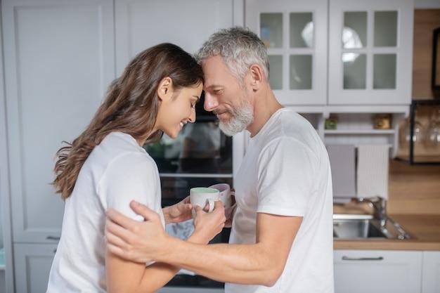 恋愛中。コーヒーを飲みながら抱き合う男女