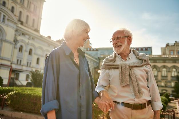 歩きながら笑顔でお互いを見ている幸せな美しい年配のカップルの愛の肖像画で