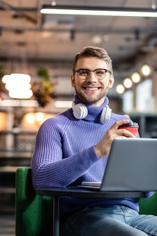 Влюблен в работу. красивый мужчина брюнетки, выражающий позитив, сидя напротив своего компьютера