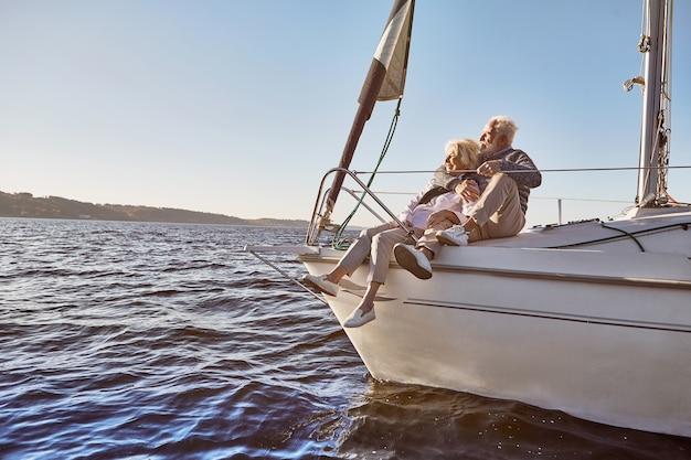 穏やかな青い海の帆船の横に座っている幸せな年配のカップルを航海するのが大好き