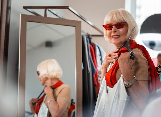 ショッピングが大好きです。新しいドレスを胸の近くに保ちながら、赤いサングラスを通して目をそらしている満足している年配の女性の腰