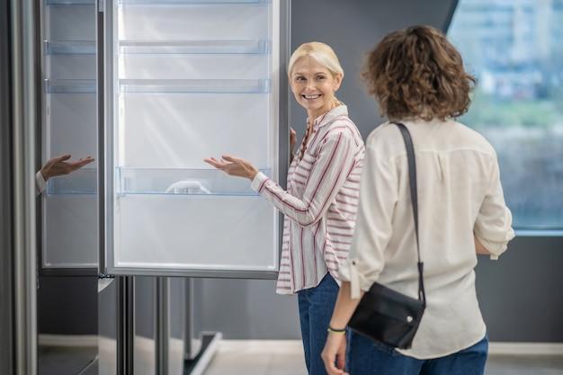 메가 스토어에서. 여성 고객에게 새 냉장고를 보여주는 스트라이프 셔츠의 영업 보조원