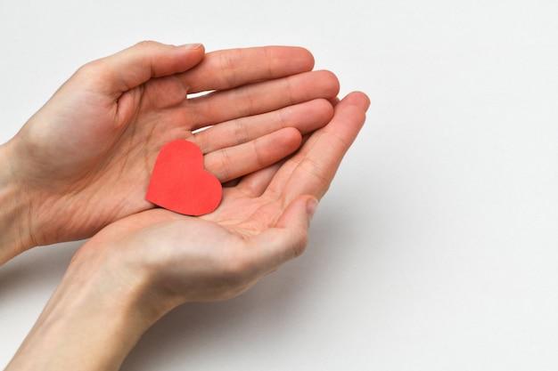 В мужских руках лежит маленькое красное сердце на сером фоне. фрагмент мужской руки.
