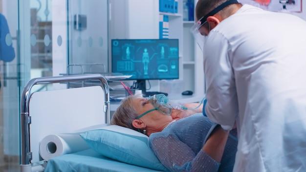 現代の病院や診療所では、医師はベッドに横たわっている高齢の患者に酸素マスクを装着しています。コロナウイルスcovid-19関連の医療医療テーマ。エピデミック時の感染症治療