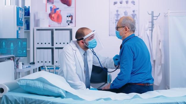 現代の私立クリニックでは、医師は病院のベッドに座っている高齢の患者の心を聞いています。病気の診断に専門的な治療を与える聴診器を使用した医療医療相談