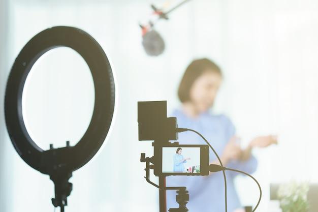 В monitor woman vlogger держит духи в руках, записывая видео для блога.