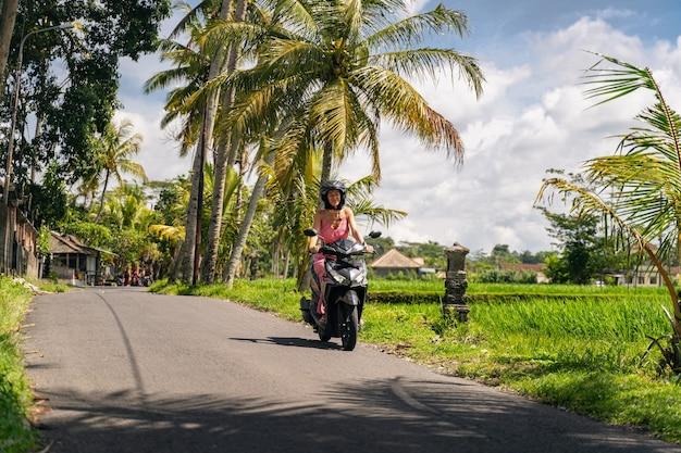 動いている。保護ヘルメットをかぶって、散歩中にカメラをまっすぐ見ている陽気な若い女性