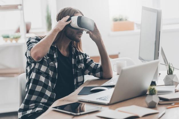 私の仮想世界で。創造的なオフィスで彼の机に座っている間彼のvrヘッドセットを調整する長い髪のハンサムな若い男