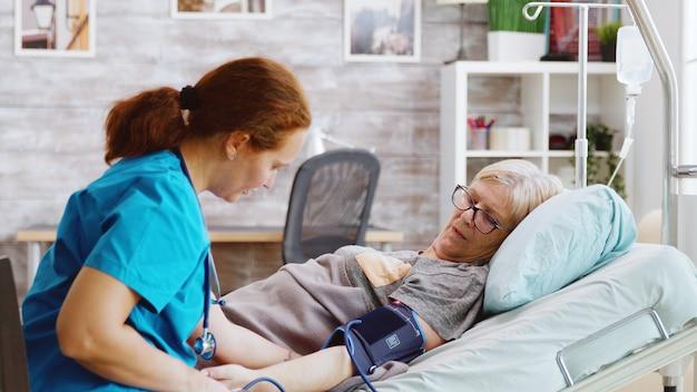 ナーシングホームでは、老婦人が若い白人看護師に血圧をチェックされます。大きな窓のある明るい部屋