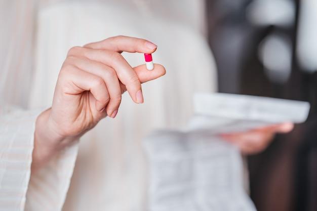 一方の手には薬の入ったカプセルがあり、もう一方の手には指示があります。