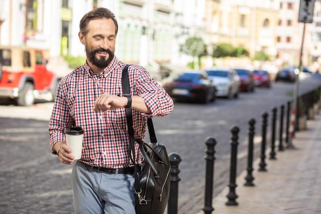 В ногу со временем. веселый красавец смотрит на свои наручные часы во время прогулки по улице