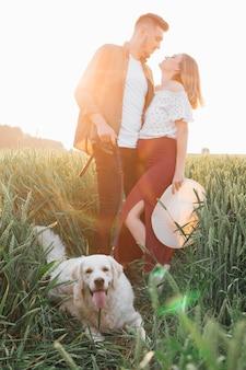 저녁 태양이 지는 광선 아래에서는 젊은 임신한 부부와 그들의 큰 흰색 개 모두가 행복합니다. 임산부 . 가족과 임신. 사랑과 부드러움. 행복과 평온. 여가 활동.