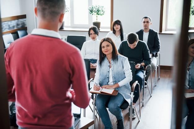 赤いシャツ。昼間の近代的な教室でのビジネス会議での人々のグループ