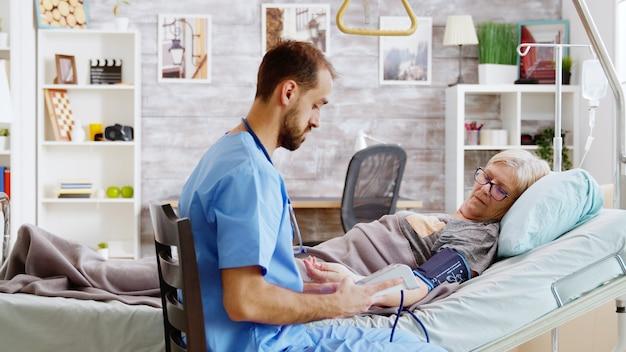 リタイヤメントホームでは、男性看護師が老婦人の血圧をチェックします。ナーシングホームワーカー
