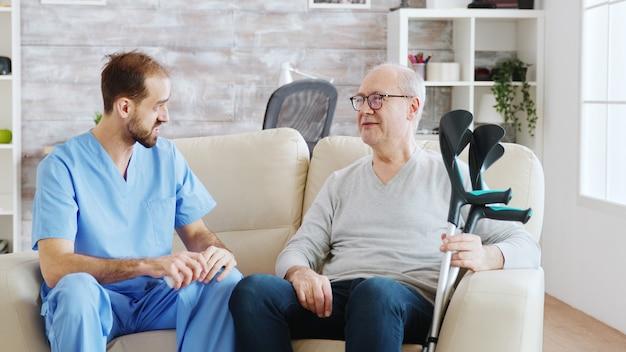 양로원에서 남자 간호사가 옆에 목발을 짚고 있는 노인과 이야기하고 있습니다. 간병인이 연금 수급자에게 약물 복용량에 대해 상담하고 있습니다.