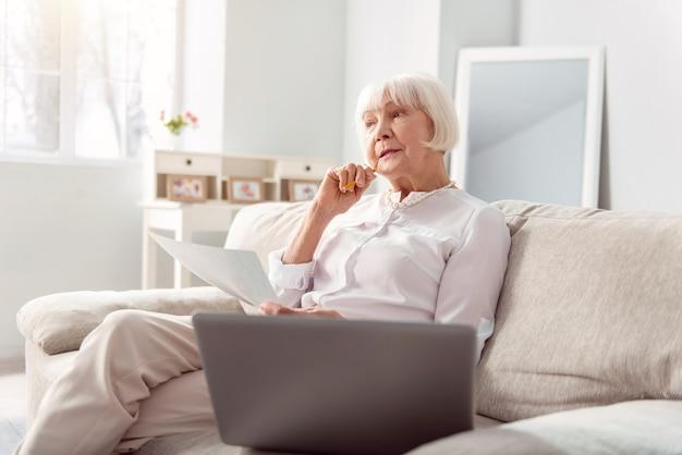 アイデアを求めて。ソファに座って深く考え、プロジェクトを改善する方法を発明する小柄な年配の女性