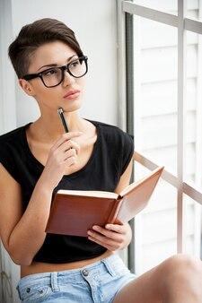 インスピレーションを求めて。メモ帳を保持し、窓枠に座っている間ペンで彼女のあごに触れる美しい若い短い髪の女性