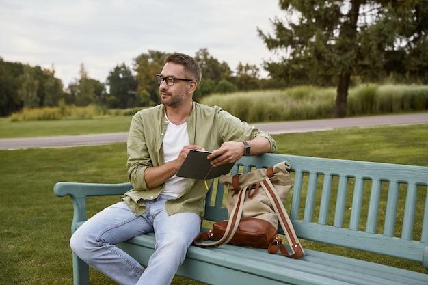 영감을 찾아 나무 벤치에 앉아 안경을 쓰고 사려깊은 젊은이