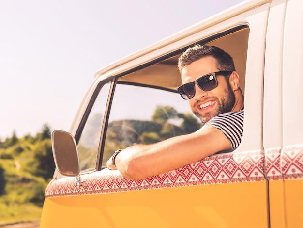 В поисках приключений. счастливый молодой человек смотрит в камеру и улыбается, сидя на переднем сиденье своего минивэна