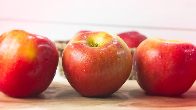 В выборочном фокусе яблока с каплями воды, на деревянной доске, размытый свет вокруг