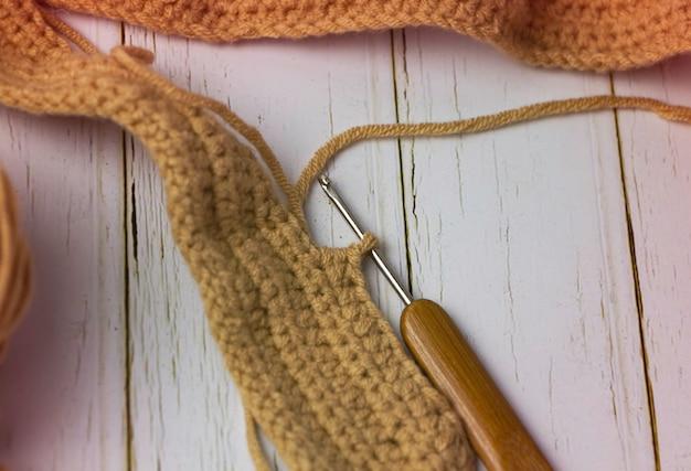かぎ針編みのフックヘッドとぼやけた編み物の選択的な焦点で、周りのぼやけた光