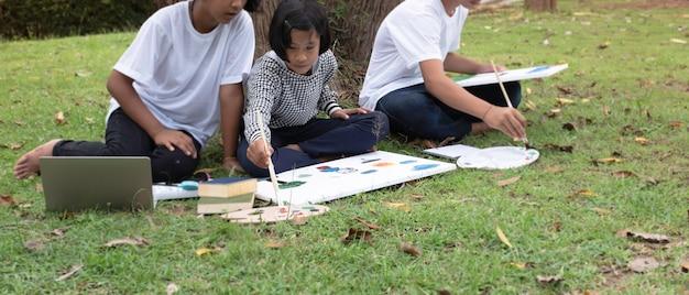 妹と弟の間に座っている少女の選択的な焦点で。キャンバスに色を塗る