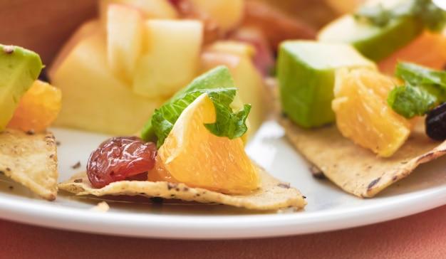 В селективном фокусе нарезанный апельсин и изюм положите крекер. самодельный из смешанных канапе фруктов, вокруг размытый свет.