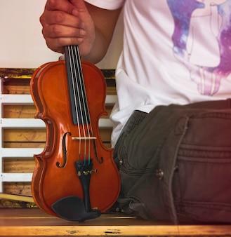 바이올린의 선택적인 초점에서 흐릿한 인간의 손, 주변의 흐릿한 빛