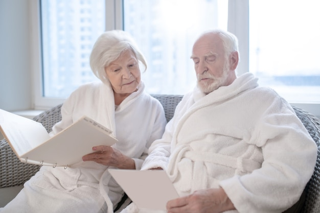 В спа-центре. пожилая пара в белых халатах, выбирая процедуры в спа-центре