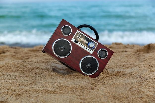라디오 녹음기 파도가 해안을 씻고 모래 위의 라디오 녹음기를 배경으로