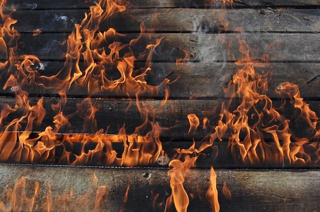 家の木板を背景に、大きな炎が燃える