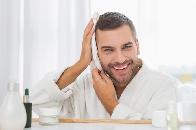バスルームで。彼の顔を拭きながら彼のタオルを持っている素敵な陽気な男