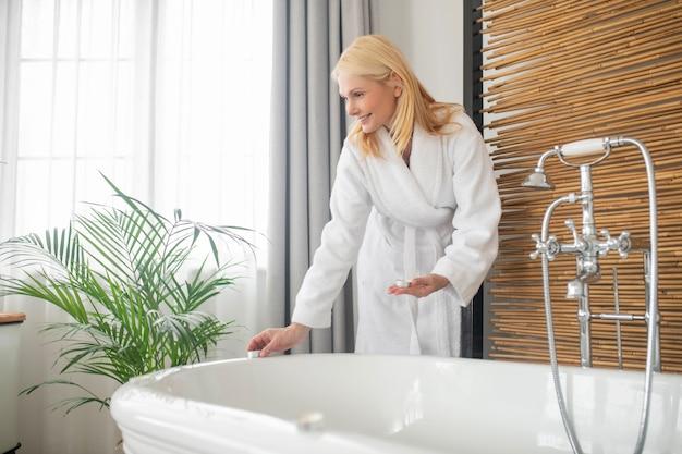 バスルームで。風呂の準備をしている白いバスローブのきれいなブロンドの女性