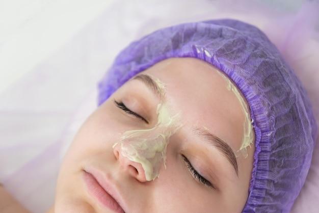 ビューティーサロンでは、美容師が少女の毎日の顔に緑色の粘土のマスクを置きます...