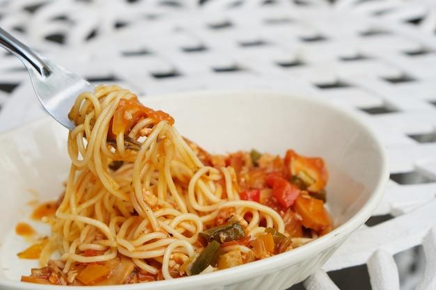 В миске кетчупа спагетти на белом столе лежит ремонтная ложка.