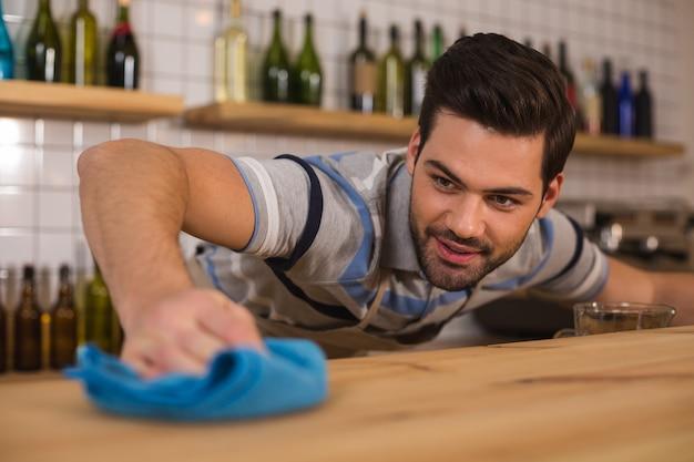 카페에서. 먼지 떨이를 들고 카페에서 일하는 동안 카운터를 청소하는 즐거운 좋은 긍정적 인 사람